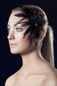 Girl with feathered accessory looks at right — Stock Photo