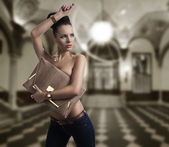 Mode brunette in jeans met grote zak en hand in de buurt van het hoofd — Stockfoto