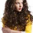 Wavy brunette with yellow jacket looks at left - Stock Photo