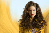 Wavy brunette with yellow jacket and hair on the shoulders — Stock Photo