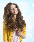 Wavy brunette with yellow jacket and hands on the breast — Stock Photo