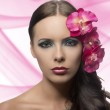 Pretty brunette with flowers near face . FLOWERS ARE FAKE — Stock Photo