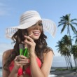 Girl in bikini smiles and drinking on palm beach — Stock Photo