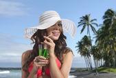 Girl in bikini smiles and drinking on palm beach — Stock Photo