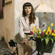 Brunette pin-up on bicycle with color flowers — Stock Photo