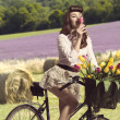 Portrait of vintage pin-up on bike smelling a flower in rural co — Stock Photo #25943435