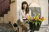 Pin up morena en bicicleta con flores de color — Foto de Stock