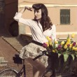 Vintage pin-up with flowers on bike in old town — Stock Photo #25979945