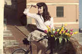 Vintage pin-up with flowers on bike in old town — Stock Photo
