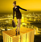 Worried business woman on gold tower and town — Stock Photo