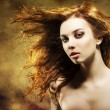 Sexy woman with flying hair on grunge background — Stock fotografie