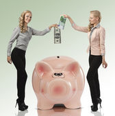 Two smiling girl saving their money euro dollar — Stock Photo
