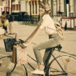 Blonde girl on bicycle in shopping time — Foto Stock