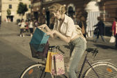 Smiling shopping girl on bicycle vintage color — Stock Photo
