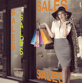 Fashion portrait of kitsch shopping girl in front of window shop — Stock Photo