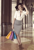 Shopping girl in fashion pose outside vintage color — Stock Photo