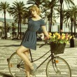 Blonde woman in sexy pose near bicycle — Stock Photo #27219375
