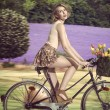 Sexy blonde girl going on the bicycle on field — Stock Photo
