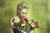Girl smelling tulips in green color — Stock Photo