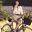 Sexy brunette girl on bicycle in rural outdoor — Stock Photo