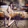 Vintage woman on bicycle in a city street with taxi — Stock Photo
