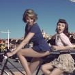 Funny vintage girls on bicycle near the sea — Stock Photo