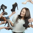 Woman surrounded by many shoes  — Stock Photo