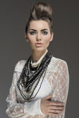 Fashion brunette with necklaces — Stock Photo