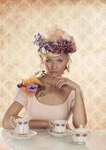 Blond meisje met klassieke thee set en hand onder de kin — Stockfoto