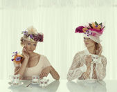 Two blonde girl with classical tea set takes tea cup — Stock Photo