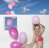 Happy woman with bikini and balloons — Stock Photo