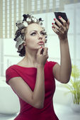 Makeup girl with hair rollers — Stock Photo