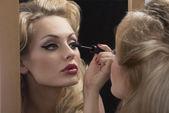 Aristocratic girl applying mascara on mirror — Stock Photo