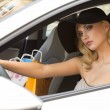 Blond elegant girl in car looking — Stock Photo