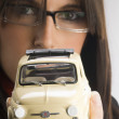 A young brunette with glasses showing a fiat — Stock Photo #4702755