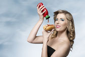 Woman with ketchup and hot-dog  — Stock Photo