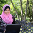 Beautiful muslim woman using laptop while sitting relaxed on bench at summer park — Stock Photo
