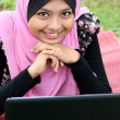 Portrait of young pretty muslim woman resting on mat at summer park using laptop — Stock Photo