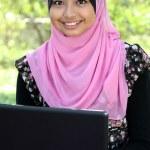 Beautiful muslim woman using laptop while sitting relaxed — Stock Photo