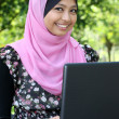Beautiful muslim woman using laptop while sitting relaxed on bench — Stock Photo #23720655