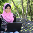 Beautiful muslim woman using laptop while sitting relaxed on bench — Stock Photo
