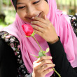 Portrait of beautiful young muslim girl holding a red rose flower — Stock Photo #23720707