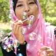 Young pretty muslim girl inflating colorful soap bubbles — Stock Photo