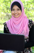 Beautiful muslim woman using laptop while sitting relaxed — Stock Photo