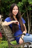 Hezká mladá žena, sedící na lavičce v podzimním parku — Stock fotografie