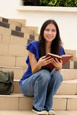 Pretty young woman reading a book at staircase — Stock Photo