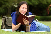 Pretty young woman reading a book at park — Stock Photo
