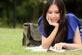 Pretty young woman reading her book at park — Stock Photo