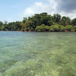 Panorama on shallow waters with a tropical island — Stock Photo