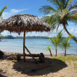 Tropical beach with thatched umbrella - Foto Stock